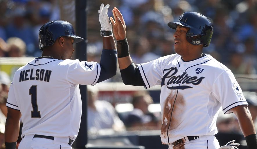 San Diego Padres' Yangervis Solarte high fives with Chris Nelson after scoring in the first inning of a baseball game against the Colorado Rockies Wednesday, Aug. 13, 2014, in San Diego. (AP Photo/Lenny Ignelzi)