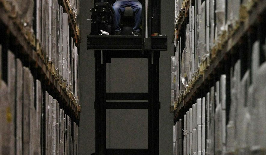In this June 18, 2014 photo, Warehouseman Harry Michael operates a narrow aisle fork lift retrieving boxes for a fork truck driver to load into a semi-trailer at Parke Warehouse in Decatur, Ill. Reinvention has kept the Decatur company business in operation. The warehouse is celebrating 160 years in business this year. (AP Photo/Herald & Review, Jim Bowling)