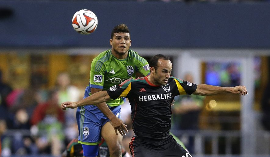 Seattle Sounders' DeAndre Yedlin, upper left, and Los Angeles Galaxy's Landon Donovan, right, go for a header in the second half of an MLS soccer match, Monday, July 28, 2014, in Seattle. Galaxy beat the Sounders 3-0. (AP Photo/Ted S. Warren)
