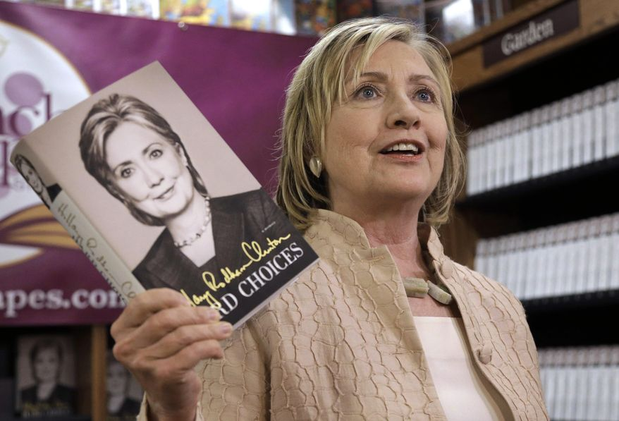 """Former Secretary of State Hillary Rodham Clinton holds her memoir """"Hard Choices"""" at Bunch of Grapes Bookstore, in Vineyard Haven, Mass., on the island of Martha's Vineyard, Wednesday, Aug. 13, 2014, during a book signing event for her memoir """"Hard Choices.""""  Hillary Rodham Clinton says she's looking forward to hugging out her differences with President Barack Obama. Obama's former secretary of state told reporters Wednesday that she's proud to have served with him despite some differences of opinion. (AP Photo/Steven Senne)"""