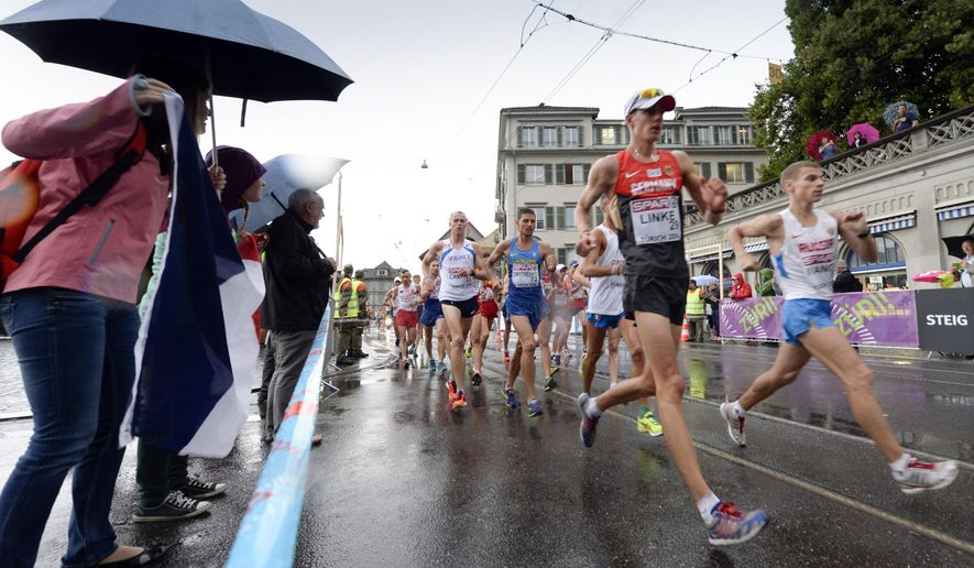 Athletes with Christopher Linke from Germany, left, compete in the men's 20km race walking in the city centre of Zurich at the second day of the European Athletics Championships in Zurich, Switzerland, Wednesday, Aug. 13, 2014. (AP Photo/Keystone, Walter Bieri)
