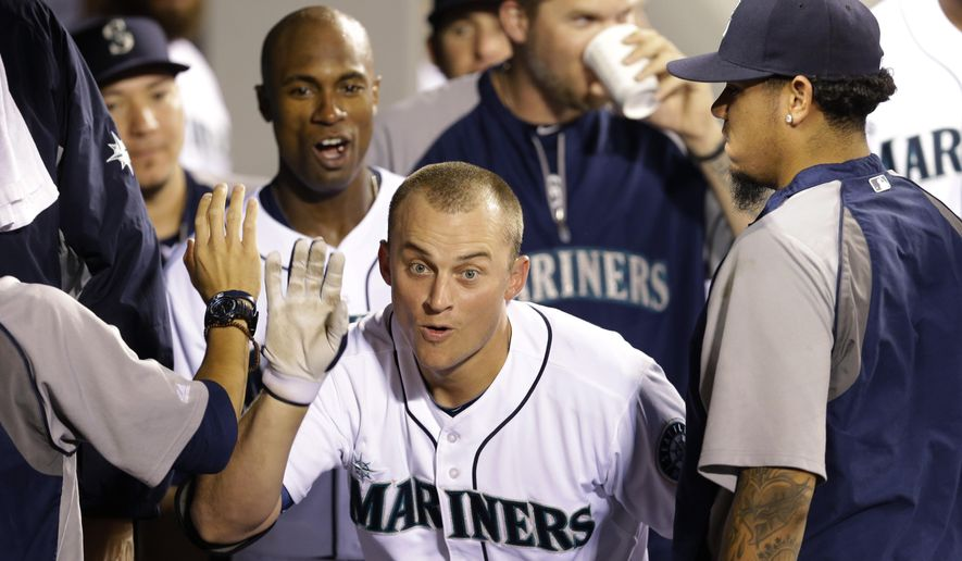 Seattle Mariners' Kyle Seager, center, celebrates with teammates, after he hit a solo home run in the fourth inning of a baseball game against the Toronto Blue Jays, Tuesday, Aug. 12, 2014, in Seattle. (AP Photo/Ted S. Warren)