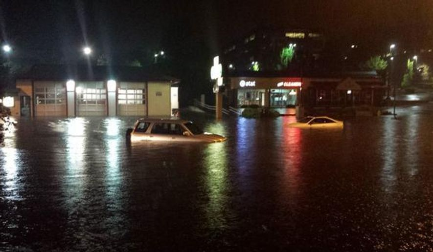 This photo provided by the Bellevue, Wash., Police Department on Wednesday, Aug. 13, 2014,, shows cars submerged under flood waters along Factoria Boulevard in Bellevue, Wash.  A long hot, dry stretch for the Seattle area was broken by a steady overnight rain that flooded some streets and caused crashes during the Wednesday morning commute. (AP Photo/Bellevue, Wash., Police Department)