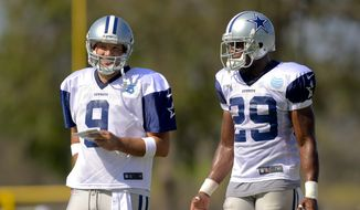 Dallas Cowboys quarterback Tony Romo (9) and teammate running back DeMarco Murray (29) talk things over at NFL training camp, Saturday, July 26, 2014, in Oxnard, Calif. (AP Photo/Gus Ruelas)
