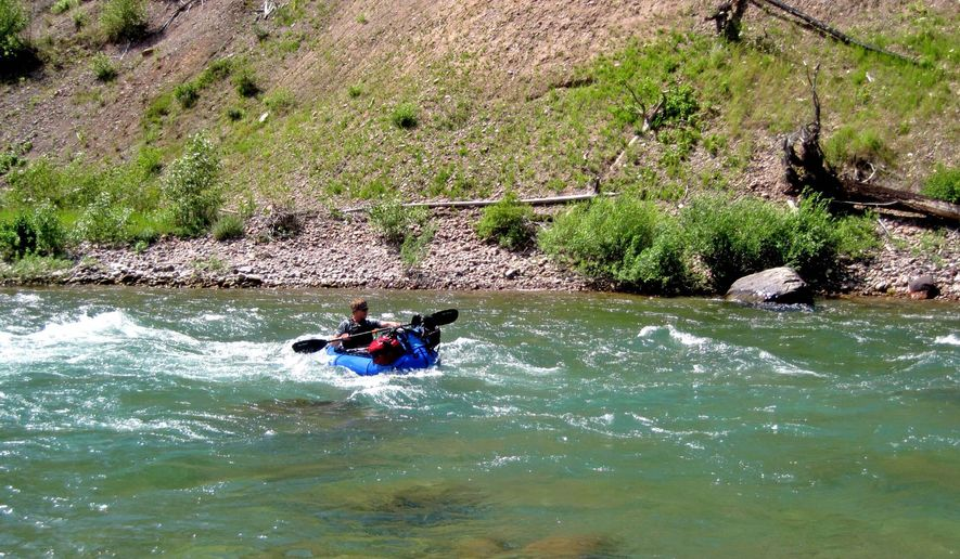 In this July 24, 2014 photo, Jared White paddles his packraft through a rapid on the South Fork Flathead River.in Mont. Packrafts allows adventurers to float wilderness rivers without needing a pack string to carry a full-sized raft, said Jared White, the Wilderness Society's regional communications manager in Bozeman. (AP Photo/The Great Falls Tribune, Erin Madison)  NO SALES