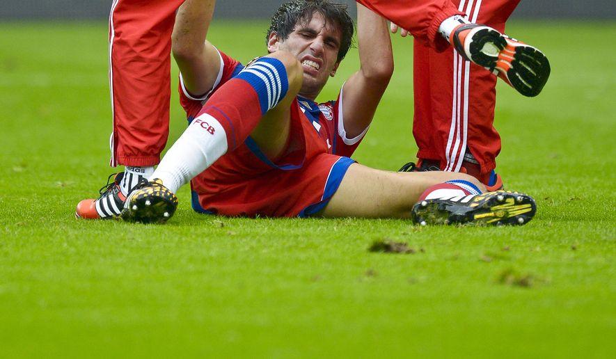 Munich's Javier Martinez lies injured on the pitch during the German soccer Super Cup match between Borussia Dortmund and Bayern Munich in Dortmund, Germany, Wednesday, Aug. 13, 2014. (AP Photo/Sascha Schuermann)