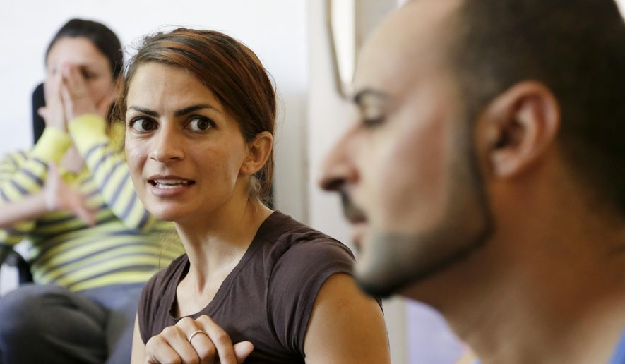 Members of the Yazidi community in LIncoln, Neb., Iekham Safar, left, her husband Ismaeil Khalaf, right, and Ismaeil's sister Gulie Khalaf, discuss the plight of the Yazidis in Iraq, Tuesday, Aug. 12, 2014, in Lincoln, Neb. Half a world away from the turmoil in Iraq, the largest concentration of Yazidis in United States is trying desperately to rescue their relatives. The first members of the religious minority group came the Lincoln, Nebraska, in the 1990s, and more than 200 families have now made it their home. The number could swell again if the group succeeds in winning asylum for the refugees who are fleeing from violence. (AP Photo/Nati Harnik)