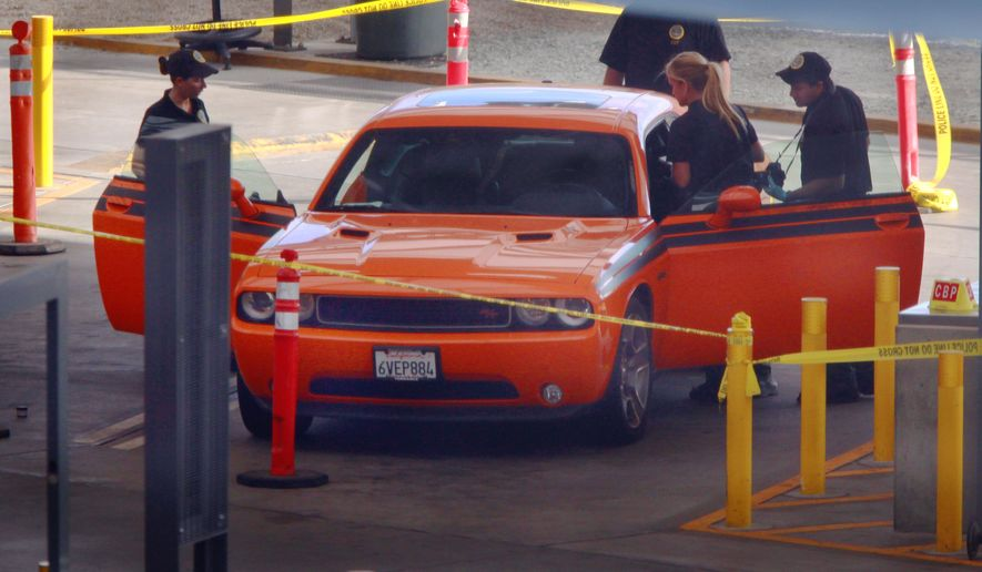 U.S. Customs and Border Protection investigators examine a car in the secondary inspection area at the San Ysidro, Calif., border crossing with Mexico, Tuesday, Aug. 12, 2014. (AP Photo/U-T San Diego, John Gastaldo) ** FILE **