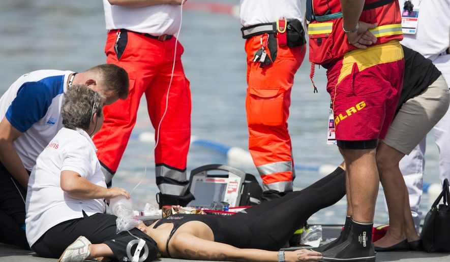 Natalia Charlos of Poland gets medical treatnebt after collapsing in the finish are of the women's 10km open water swim competition at the LEN Swimming European Championships in Berlin, Germany, Wednesday, Aug. 13, 2014. (AP Photo/Gero Breloer)