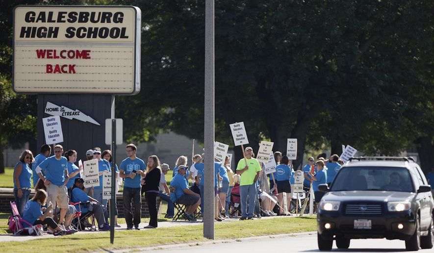 Teachers walk a picket line in front of Galesburg High School in Galesburg, Ill., Wednesday, Aug. 13, 2014, after the Galesburg Education Association turned down a contract offer late Tuesday from District 205 after more than 15 hours of mediation in the past two days. It's the first strike in Galesburg in 37 years. School is scheduled to start Thursday. (AP Photo/The Register-Mail, Steve Davis)