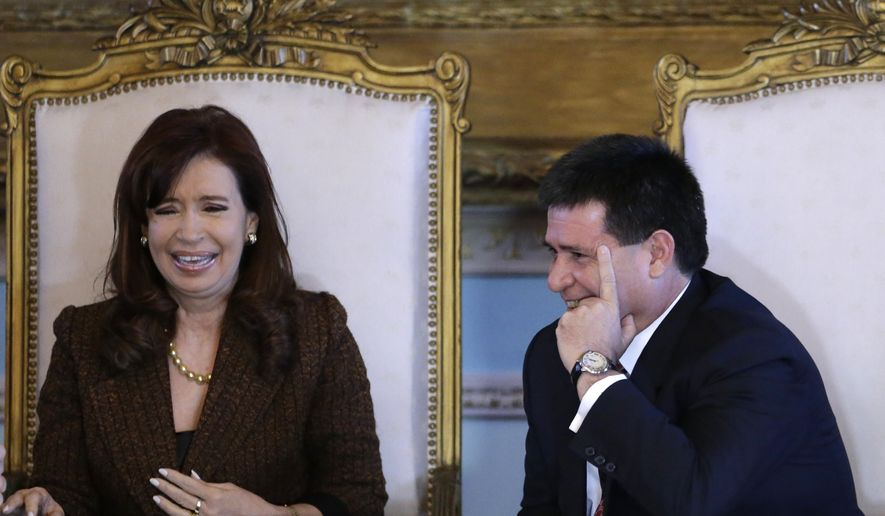 Argentina's President Cristina Fernandez and Paraguay's President Horacio Cartes, attend an official ceremony at the Palacio de Lopez, in Asuncion, Paraguay, Wednesday, Aug 13, 2014. Fernandez is on an official visit that includes the return of furniture and other belongings confiscated by Argentine forces during the Triple Alliance War, between 1864-1870. (AP Photo/Jorge Saenz)