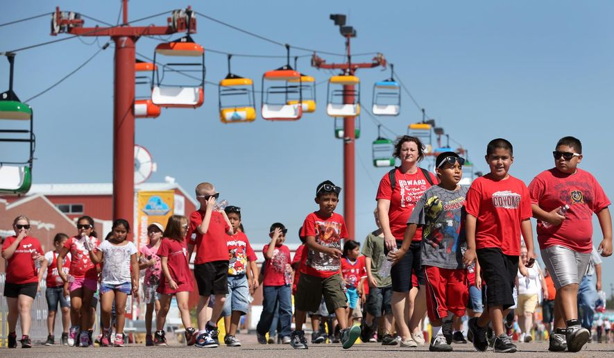 In this photo from Aug. 27, 2013, Howard Elementary students walk through the fairgrounds at the State Fair in Grand Island, Neb. The Nebraska State Fair's new home in Grand Island places it closer to the center of the state, but the move from Lincoln four years ago has created a potential opening for Iowa. Both fairs are advertising to Omaha residents, but organizers say they aren't competing. They argue that the fairs are scheduled at different times of the month, and offer different concerts and events. (AP Photo/The Grand Island Independent, Barrett Stinson)