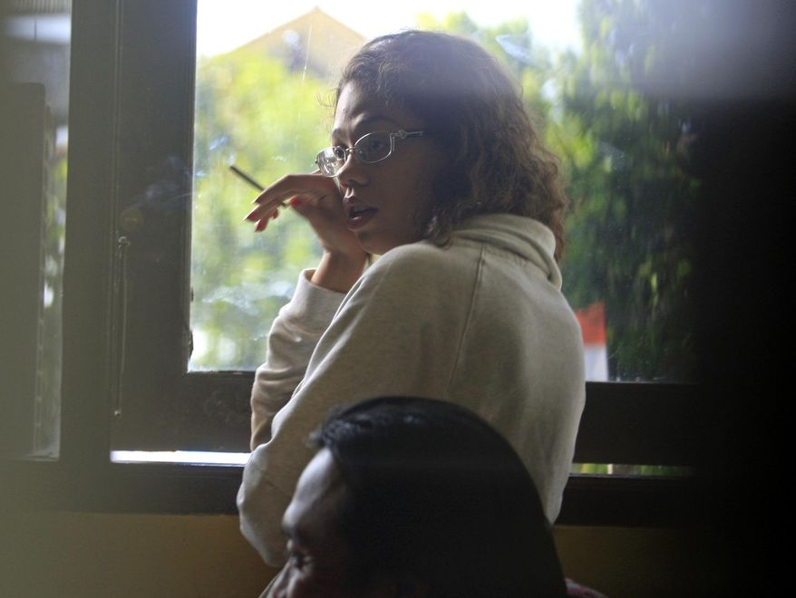Heather Mack, stands at the police district headquarters after she was brought in for questioning in relation to the death of her mother, in Bali, Indonesia, Thursday, Aug. 14, 2014. The body of Sheila von Wiese-Mack, a 62-year-old American woman, was found stuffed inside a suitcase on the Indonesian resort island of Bali, and authorities on Wednesday arrested her daughter and her daughter's boyfriend in relation to the death, police said. The suitcase containing Mack's body was found Tuesday inside the trunk of a taxi parked in front of the St. Regis Bali Resort in the island's upscale Nusa Dua area, said Col. Djoko Hari Utomo, the police chief in Bali's capital, Denpasar. (AP Photo/Firdia Lisnawati)