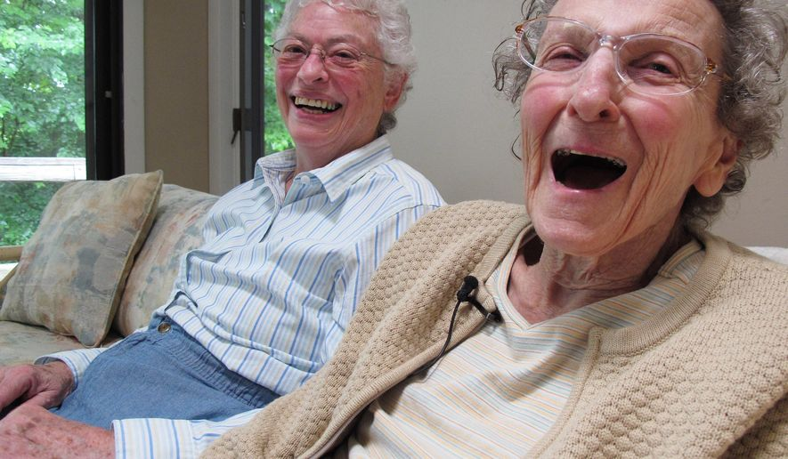 In this Friday, Aug. 1, 2014 photo, Lennie Gerber, left, and her spouse, Pearl Berlin, laugh while at their home in High Point, N.C. The couple, who have been together 48 years and legally married in Maine in 2013, have a federal challenge pending against North Carolina's constitutional amendment banning gay marriage. (AP Photo/Allen G. Breed)