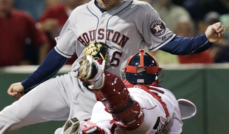 Boston Red Sox catcher Christian Vazquez tags out Houston Astros' Jake Marisnick, who tried to score on a fly out to right field by Jose Altuve, during the seventh inning of a baseball game at Fenway Park in Boston, Thursday, Aug. 14, 2014. (AP Photo/Charles Krupa)