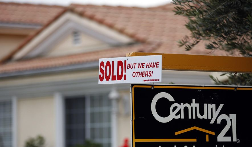 FILE - This Jan. 23, 2013 file photo shows a real estate sign in front of  a home in Downey, Calif. California home sales declined in July 2014 compared to the same time the previous year as buyers struggled to find something they could afford in the tight market, a research firm said Thursday, Aug. 14, 2014. (AP Photo/Jae C. Hong, File)