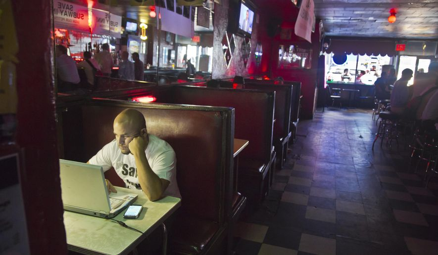 Steven Salinas works at his laptop in a booth at the family owned Subway Inn Bar on Thursday Aug. 14, 2014 in New York. The Subway Inn, one of Manhattan's infamous dive bars, is set to close later this month to make way for high-end luxury condos. But the family that has run the 77-year-old bar for the past 40 years is not going down easy. They are calling on the city to declare the building a landmark and stop the wrecking ball. (AP Photo/Bebeto Matthews)