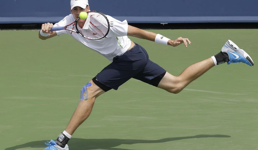 John Isner returns a serve against Andy Murray, from Great Britain, during a match at the Western & Southern Open tennis tournament, Thursday, Aug. 14, 2014, in Mason, Ohio. (AP Photo/Al Behrman)