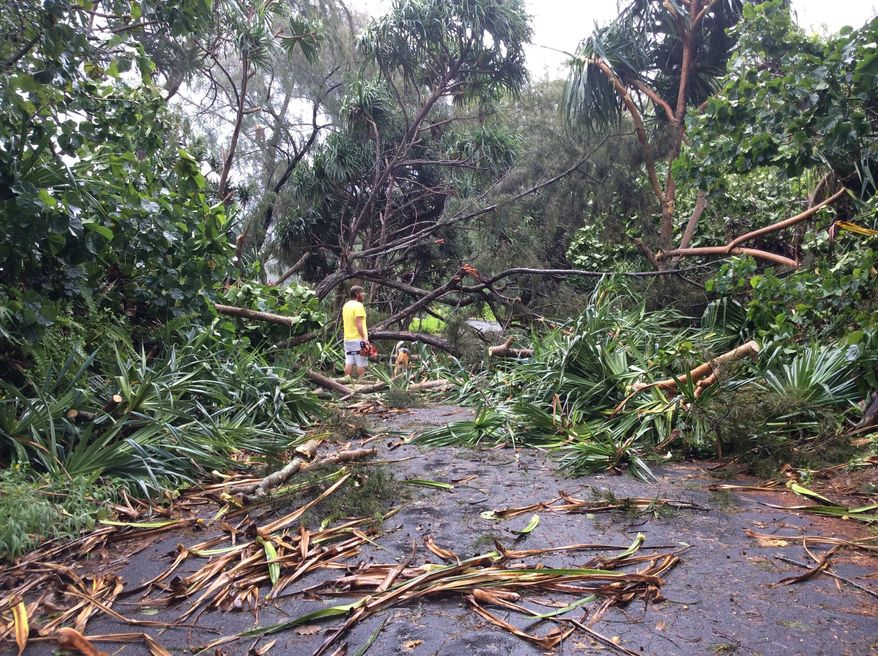 In this Friday, Aug. 8, 2014 photo, Andrew Fujimura, 29, works to clear a roadway in Puna, Hawaii where wind and rain knocked out power and isolated thousands of residents. (AP Photo/Andrew Fujimura) NO SALES