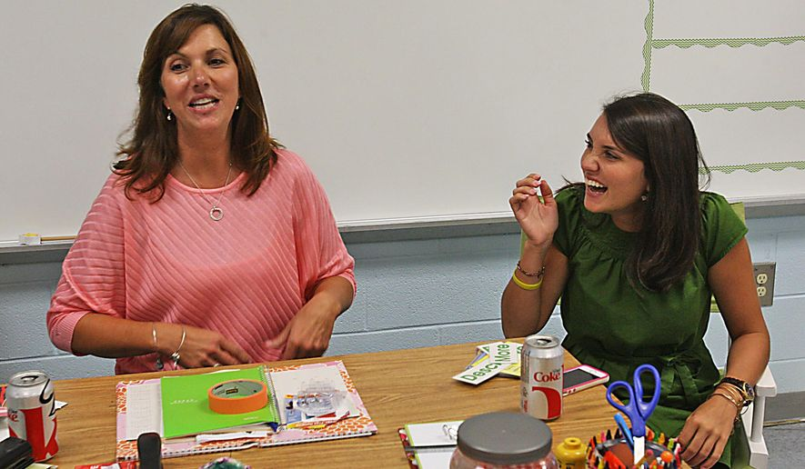 ADVANCE FOR RELEASE SUNDAY, AUG. 17, 2014, AND THEREAFTER - In this Aug. 7, 2014 photo, first-year Windsor Hill Arts Infused Elementary School teachers Kristi Bryan, left, and her daughter, Katie Lynch, sit in a classroom at the school, in North Charleston, S.C. Bryan teachers fourth grade and Lynch teaches first grade. (AP Photo/The Post and Courier, Leroy Burnell)