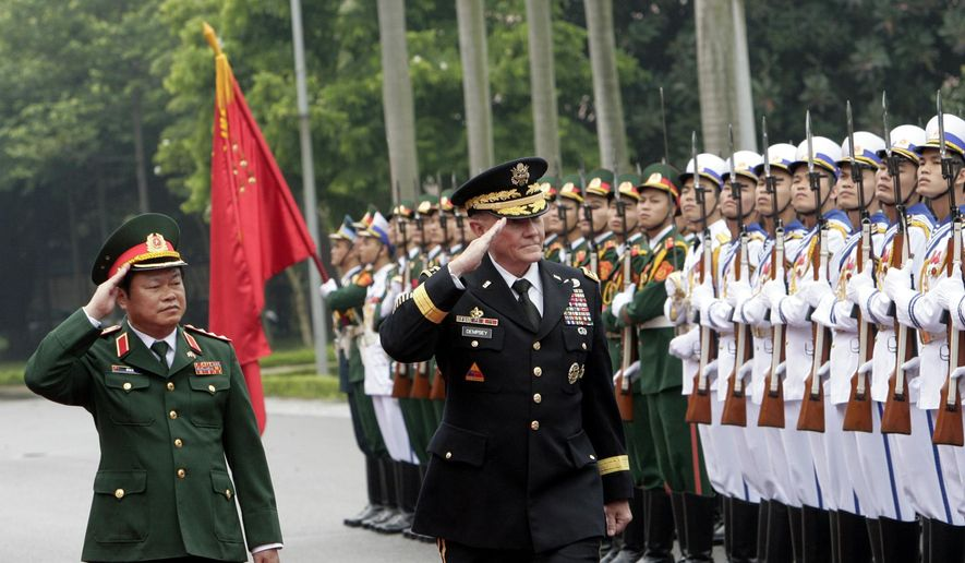 U.S. Chairman of the Joint Chiefs of Staff, Gen. Martin Dempsey, right, and Vietnamese Chief of General Staff of the Army, Lt. Gen. Do Ba Ty, left, review an honor guard before their talks in Hanoi, Vietnam on Thursday Aug. 14, 2014. Dempsey will hold talks with Vietnamese defense officials Wednesday on a visit that aims to boost military ties between the two former foes. (AP Photo/Tran Van Minh)