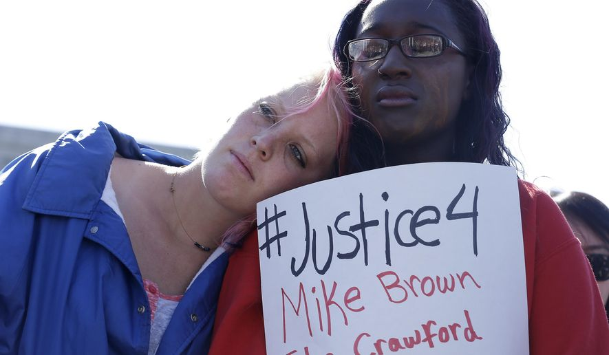Savannah McCoy, 17, right, holds up a sign as she and her friend Kimber Camgros, 16, listen to speakers during a vigil for Michael Brown of Ferguson, Mo., in San Francisco, Thursday, Aug. 14, 2014. Brown, an unarmed black teenager, was killed by a white police officer on Saturday, Aug. 9, 2014. (AP Photo/Jeff Chiu)