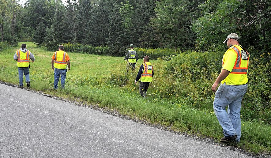 Officials search a roadside field in Oswegatchie, N.Y., on Thursday, Aug. 14, 2104, for clues in the abduction of two Amish girls who were taken from a vegetable stand on the evening before. Amish sisters Delila, 6 and Fannie Miller, 12, were abducted on about 7:30 p.m., Wednesday evening from a vegetable stand in front of their home. (AP Photo/Watertown Daily Times, Melanie Kimber-Lago)