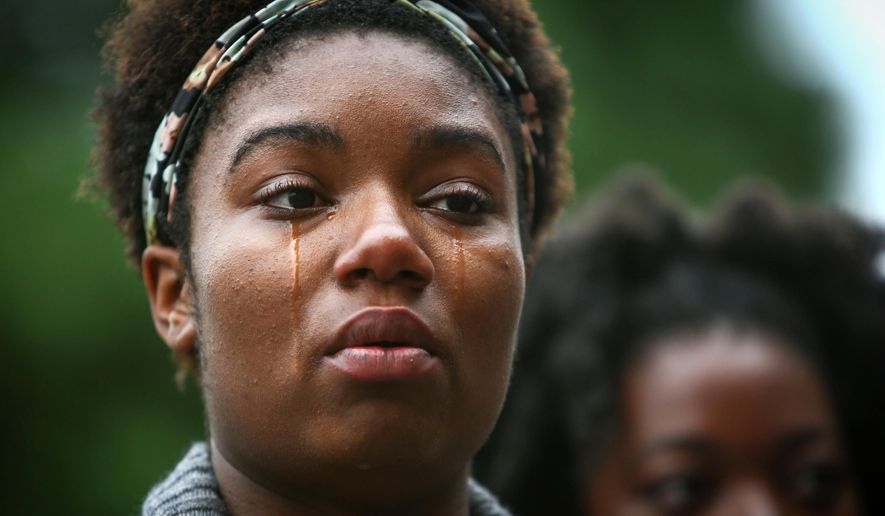 Zenobia Taylor, 17, becomes emotional during a National Moment of Silence gathering Thursday, Aug. 14, 2014, in Seattle. People in more than 90 cities observed Thursday's National Moment of Silence. The vigils come in the wake of the shooting death of an 18-year-old man by a police officer in Ferguson, Missouri, and the death of a New York City man caused by a police officer's chokehold. (AP Photo/seattlepi.com, Joshua Trujillo)