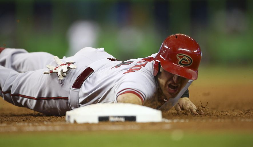 Arizona Diamondbacks' Cliff Pennington dives back on a pick off attempt by Miami Marlins' Brad Penny during the second inning of a baseball game in Miami, Thursday, Aug. 14, 2014. (AP Photo/J Pat Carter)