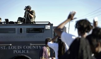 A member of the St. Louis County Police Department points his weapon in the direction of a group of protesters in Ferguson, Mo. on Wednesday, Aug. 13, 2014. On Saturday, Aug. 9, 2014, a white police officer fatally shot Michael Brown, an unarmed black teenager, in the St. Louis suburb. (AP Photo/Jeff Roberson)