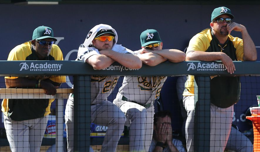 Members of the Oakland Athletics watch from the dugout during the ninth inning of a baseball game against the Kansas City Royals Thursday, Aug. 14, 2014, in Kansas City, Mo.  The Royals won 7-3. (AP Photo/Ed Zurga)