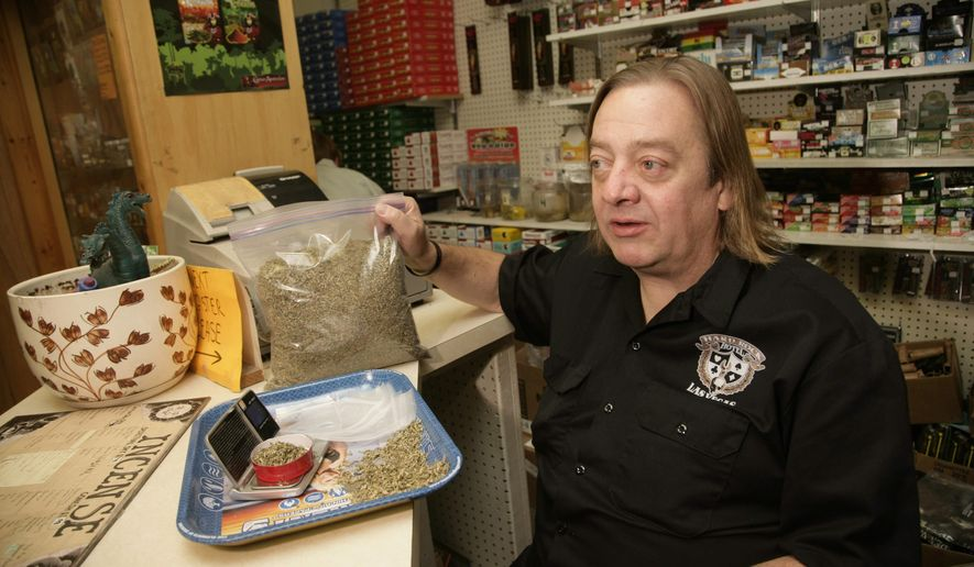 """FILE -  In this Sept. 21, 2011, file photo, Jim Carlson, owner of Last Place On Earth, a head shop that openly sold synthetic drugs, holds a bag of """"No Name"""" synthetic drugs in his store in Duluth, Minn. Carlson is scheduled to be sentenced in federal court on Thursday, Aug. 14, 2014. Prosecutors are seeking a 20-year sentence against Carlson, who was convicted on 51 felony counts last October. (AP Photo/Paul M. Walsh,File)"""