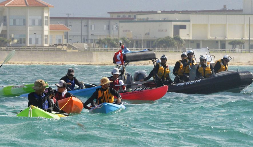 Anti US base protesters in canoe are blocked by a Japan Coast Guard speed boat in Nago, Okinawa, southern Japan, Thursday, Aug. 14, 2014. Japanese officials said buoys are being floated off the southernmost island of Okinawa in one of the first steps in the relocation of an American military base. The buoys define the area where the construction will begin on a facility in coastal Henoko that will house the Marine Corps Air Station Futenma, which will be relocated from a crowded residential area of Okinawa. (AP Photo/Kyodo News) JAPAN OUT
