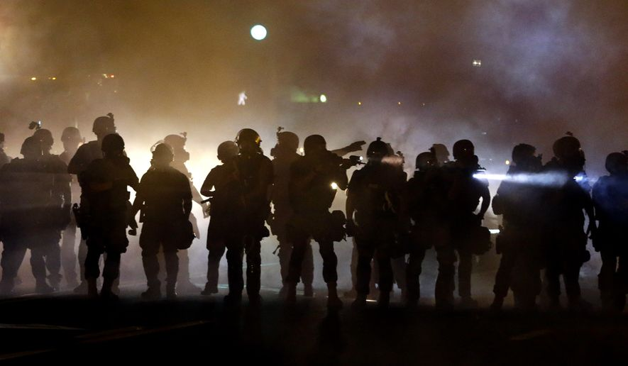 Police walk through a cloud of smoke as they clash with protesters Wednesday, Aug. 13, 2014, in Ferguson, Mo.  (AP Photo/Jeff Roberson)