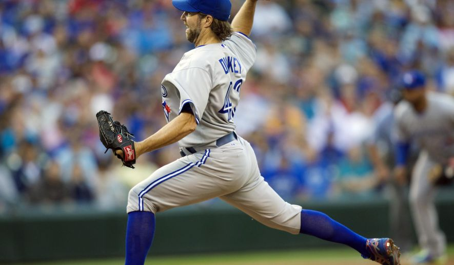 Toronto Blue Jays starter R.A. Dickey delivers a pitch during the first inning of a baseball game against the Seattle Mariners, Wednesday, Aug. 13, 2014, in Seattle. (AP Photo/Stephen Brashear)