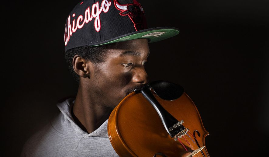ADVANCE FOR SATURDAY, AUG. 16 - Violinist Dextorist Timmons poses for a photo July 21, 2014, in Fayetteville, N.C. Timmons is leaving Fayetteville for Elizabeth City State University, where he plans to study music performance. (AP Photo/The Fayetteville Observer, Abbi O'Leary) MAGS OUT, NO SALES