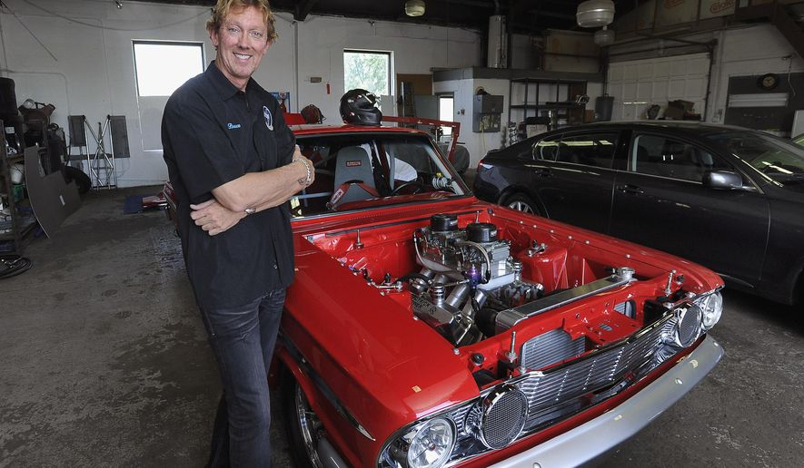 In this June 15, 2014 photo, Bruce Jones, of Elmhurst, Ill., poses with his 1964 Ford Thunderbolt Fairlane showcar/drag racing car. Jones, whose day job is as a CPA, got the racing bug eight years ago. (AP Photo/Daily Herald, Mark Welsh)  MANDATORY CREDIT, MAGS OUT