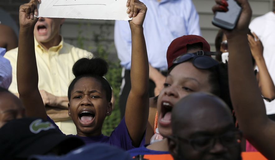 Demonstrators at the site where Michael Brown was shot and killed by police in Ferguson, Missouri. News crews reporting on the events have been targeted by police, as have protesters. (AP Photo/Jeff Roberson)