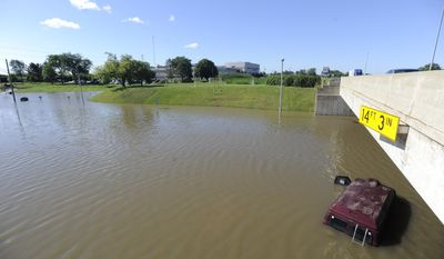 In this photo taken on Wednesday, Aug. 13, 2014, vehicles are submerged under floodwaters in front of Baker College along Outer Drive near Interstate 94 in Allen Park, Mich. Michigan Gov. Rick Snyder has declared a state of disaster in the Detroit area after heavy rain caused major road closures, flooded houses and damaged infrastructure. (AP Photo/Detroit News, David Coates) DETROIT FREE PRESS OUT, HUFFINGTON POST OUT, MAGS OUT, MANDATORY CREDIT