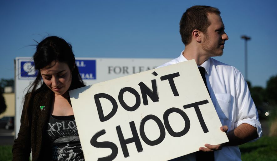 Protesters hold a sign in front of the Vatterott College campus in St. Joseph, Mo. on Thursday, Aug. 14, 2014 in support of Michael Brown of Ferguson, Mo. On Saturday, Aug. 9, 2014, a white police officer fatally shot Brown, an unarmed black teenager, in the St. Louis suburb. (AP Photo/St. Joseph News-Press, Sait Serkan Gurbuz)