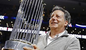 FILE - In this Nov. 1, 2013, file photo, Boston Red Sox Chairman Tom Werner holds the World Series trophy on the court before an NBA basketball game between the Boston Celtics and the Milwaukee Bucks in Boston. Baseball's 30 owners will meet in Baltimore this week to vote on Major League Baseball Commissioner Bud Selig's replacement. A seven-man committee whittled down an expansive list to three candidates: MLB Chief Operating Officer Rob Manfred, Boston Red Sox Chairman Tom Werner and MLB Executive Vice President of Business Tim Brosnan. (AP Photo/Michael Dwyer, file)