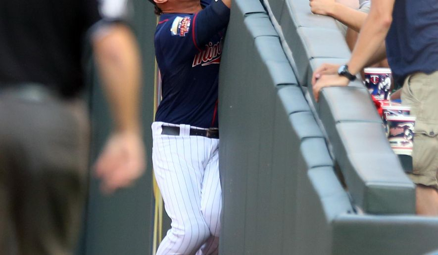 Minnesota Twins right fielder Oswaldo Arcia makes a futile attempt up the wall for a foul ball by Kansas City Royals catcher Salvador Perez in the first inning of a baseball game, Friday, Aug. 15, 2014, in Minneapolis. (AP Photo/Jim Mone)