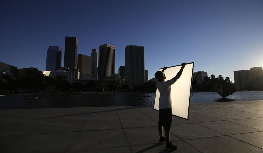 FILE - In this photo taken on Thursday, Aug. 14, 2014, production assistant Adrien Noriega holds a reflector before a film shoot outside the Department of Water and Power headquarters in Los Angeles. Hoping to keep film productions from fleeing California for other states and countries, lawmakers have moved to quadruple tax subsidies for location shooting. (AP Photo/Jae C. Hong, File)