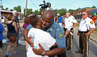 Capt. Ronald Johnson of the Missouri Highway Patrol hugs Angela Whitman, of Berkeley, Mo., on West Florissant Avenue in Ferguson, Mo., on Thursday, Aug. 14, 2014. The Missouri Highway Patrol seized control of the St. Louis suburb Thursday, stripping local police of their law-enforcement authority after four days of clashes between officers in riot gear and furious crowds protesting the death of an unarmed black teen shot by an officer. (AP Photo/St. Louis Post-Dispatch, David Carson)