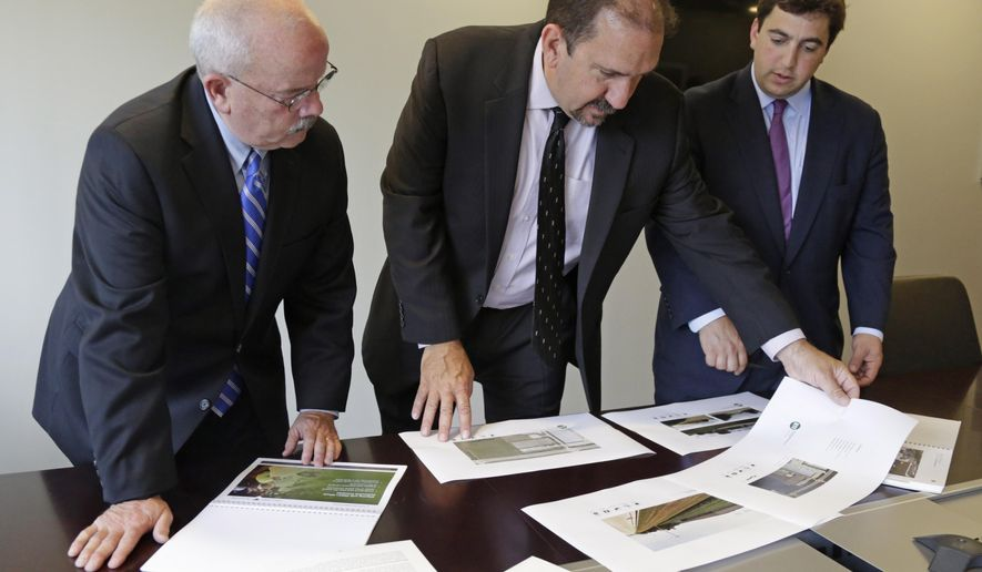 In this photo taken on Aug. 13, 2014, Kenneth Bouch, center, and Ben Kovler, right, of Green Thumb Industries, an Illinois-based partnership of medical marijuana entrepreneurs, review security plans for a proposed medical marijuana facility with security adviser Terry Gainer during a meeting in Chicago. Medical marijuana in Illinois will be encased in vaults, monitored by security guards and protected by fingerprint-recognition biometrics. That's the picture painted by business owners who are competing for a limited number of marijuana cultivation and dispensary permits under the state's new law. A detailed security plan will give an edge in the scoring, so many of the applicants say they're exceeding the Illinois law's already-strict requirements.(AP Photo/M. Spencer Green)
