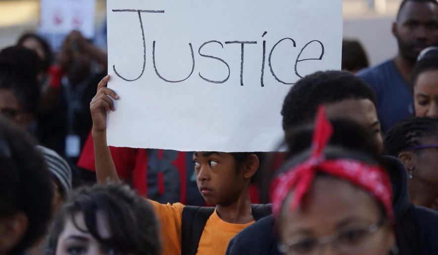 A child holds a sign during a vigil at Hart Plaza in downtown Detroit on Thursday, Aug.14, 2014,  for Michael Brown who was shot by a police officer in Ferguson, Mo. (AP Photo/Detroit Free Press, Ryan Garza)