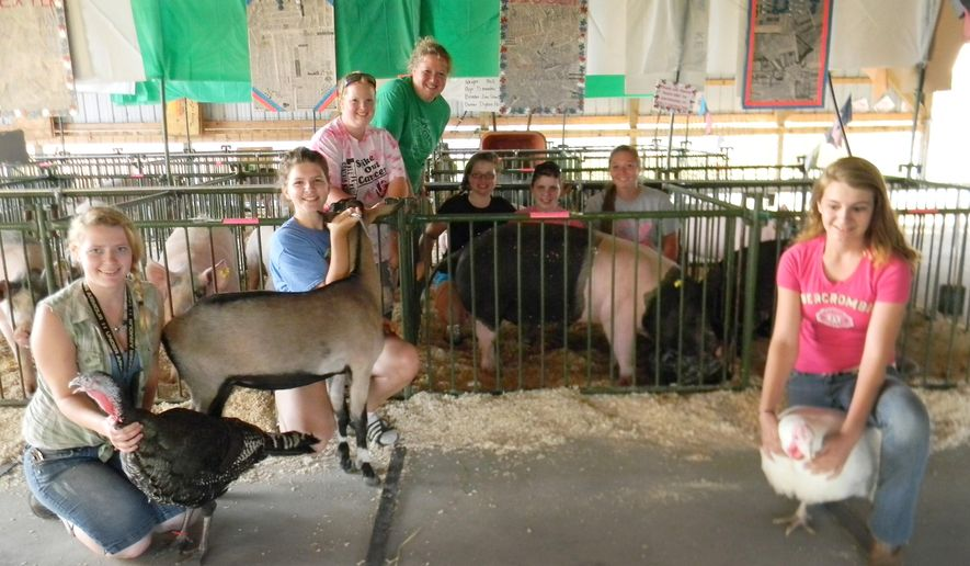 "In a photo taken on Aug. 10, 2014, the Udell family poses with their animals at the Alpena County Fair in Alpena, Mich. The family has been involved with 4-H for over 30 years, and in that 30 years, Tricia Udell has never missed one Alpena County Fair. Udell started showing animals at the fair when she was old enough to be a 4-H member, and has since had all of her children involved in the fair, which ends Saturday, and the program. ""The fair and 4-H is such a positive experience for kids,"" she told The Alpena News. It really teaches you responsibility, leadership, and how to take pride in your work."" (AP Photo/The Alpena News, Nicole Grulke)"
