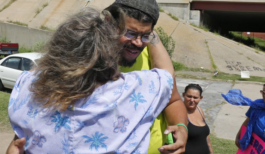Pam Wilkins hugs Carl Morse, father of shooting victim Jeremey Lake, as he arrives for a memorial rally for the teenager in Tulsa, Okla. on Friday, Aug. 15, 2014. Off-duty police officer Shannon Kepler is accused of fatally shooting the 19-year old after he saw Lake walking with his daughter on Aug. 5, 2014. Lake was the nephew of Wilkins and the son of Morse. (AP Photo/Sue Ogrocki)
