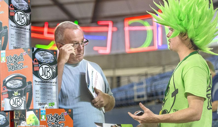 """Dale Rennaker of Vancouver talks with Chris Whitener, a Magic Butter company service representative about the MB2 magical butter machine during the first """"Cannacon"""" convention Thursday, Aug. 14, 2014, at the Tacoma Dome in Tacoma, Wash. (AP Photo/ The News Tribune, Dean Koepfler)"""