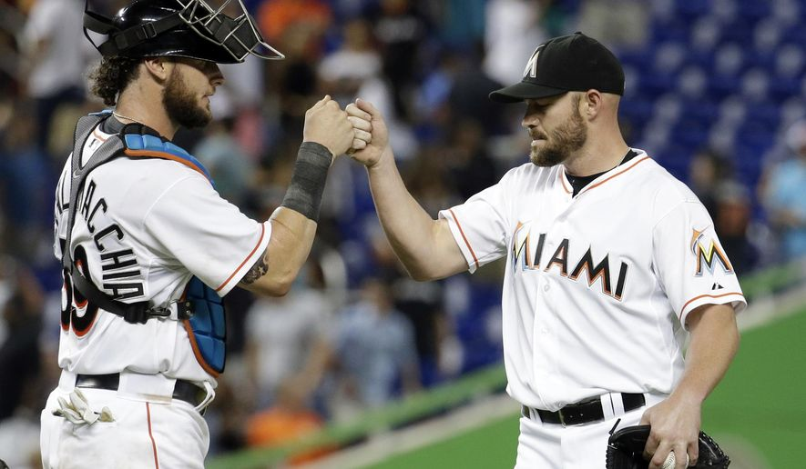 Miami Marlins catcher Jarrod Saltalamacchia (39) and relief pitcher Mike Dunn, right, bump fists after the Marlins defeated the St. Louis Cardinals 3-0 during a baseball game, Tuesday, Aug. 12, 2014, in Miami. (AP Photo/Lynne Sladky)